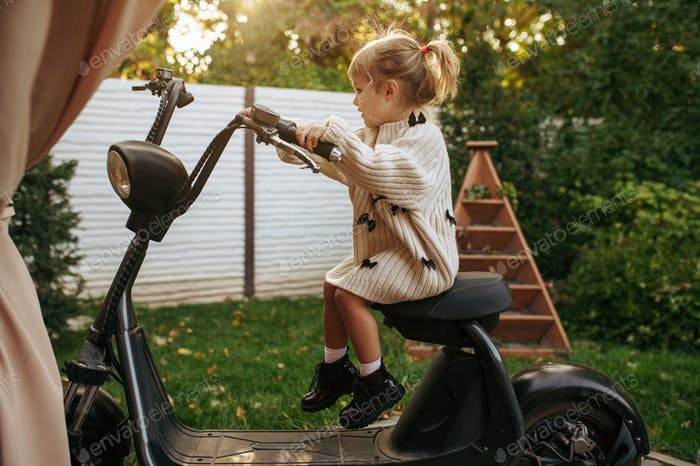 Little girl sitting on vintage scooter in garden