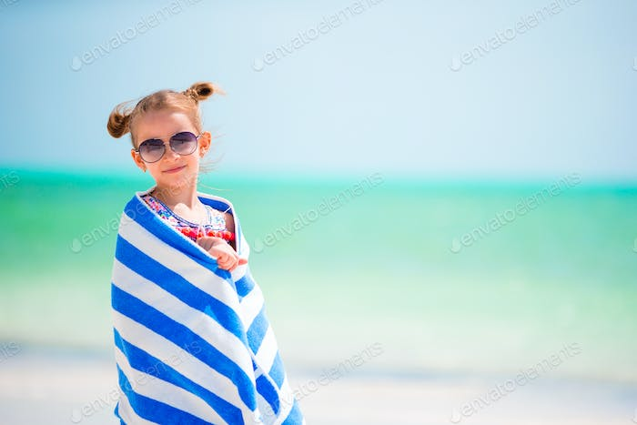 Adorable little girl wrapped in towel after swimming at tropical beach