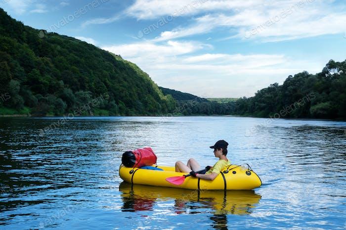 Tourist auf gelbem Packraft-Schlauchboot mit rotem Padle