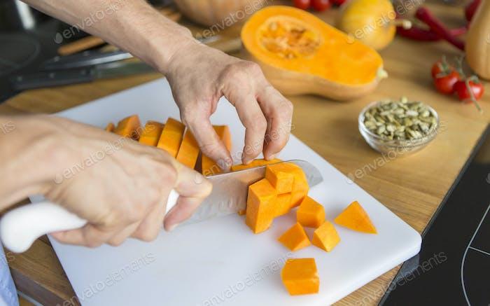 Man cutting pumpkin for making vegetarian dish cream soup