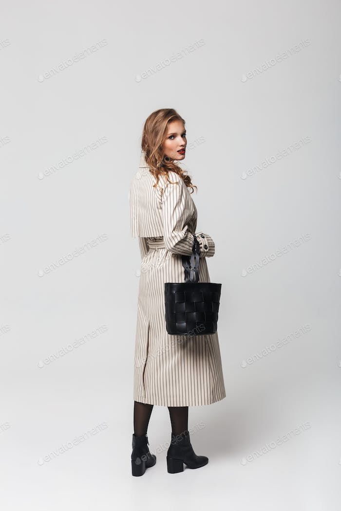 Young attractive woman with wavy hair in striped coat holding black bag dreamily looking in camera