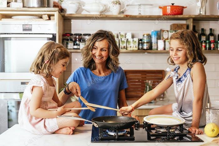 Kleine Schwestern kochen mit ihrer Mutter in der Küche.