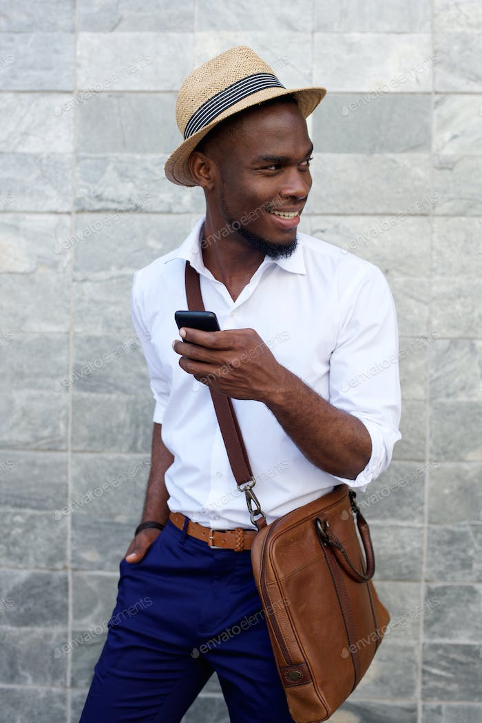 Smiling young black man with mobile phone and bag
