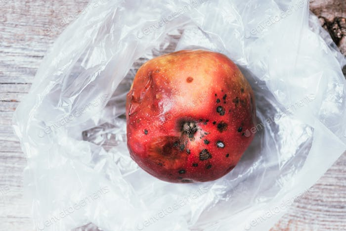 Spoiled bad red apple on plastic bag background. Garbage dump rotten food. Top view. Copy space