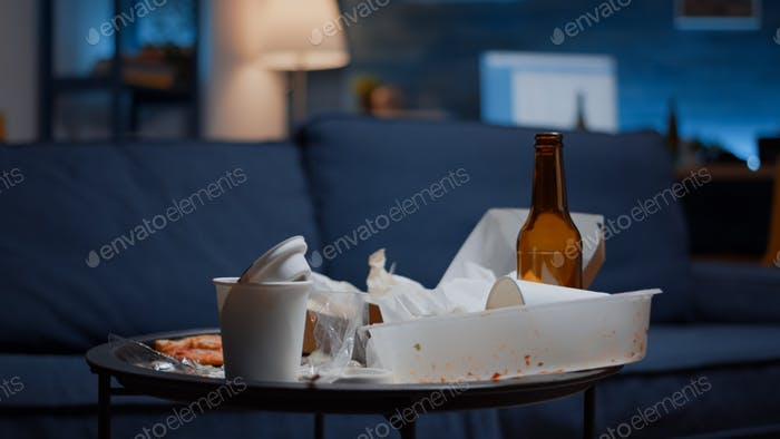 Messy empty living room of depressed person with scattered food mess