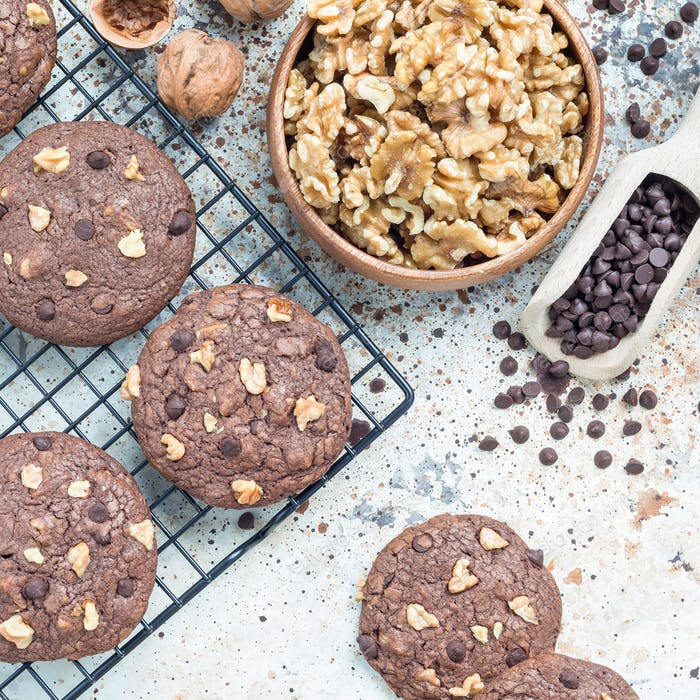 Chocolate cookies with walnuts and chocolate chips on table and cooling rack, top view, square