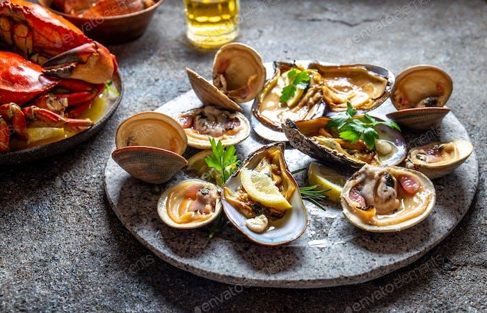 Mariscos crudos, cangrejos, almejas y mejillones mariscos con limón y cilantro sobre placa gris