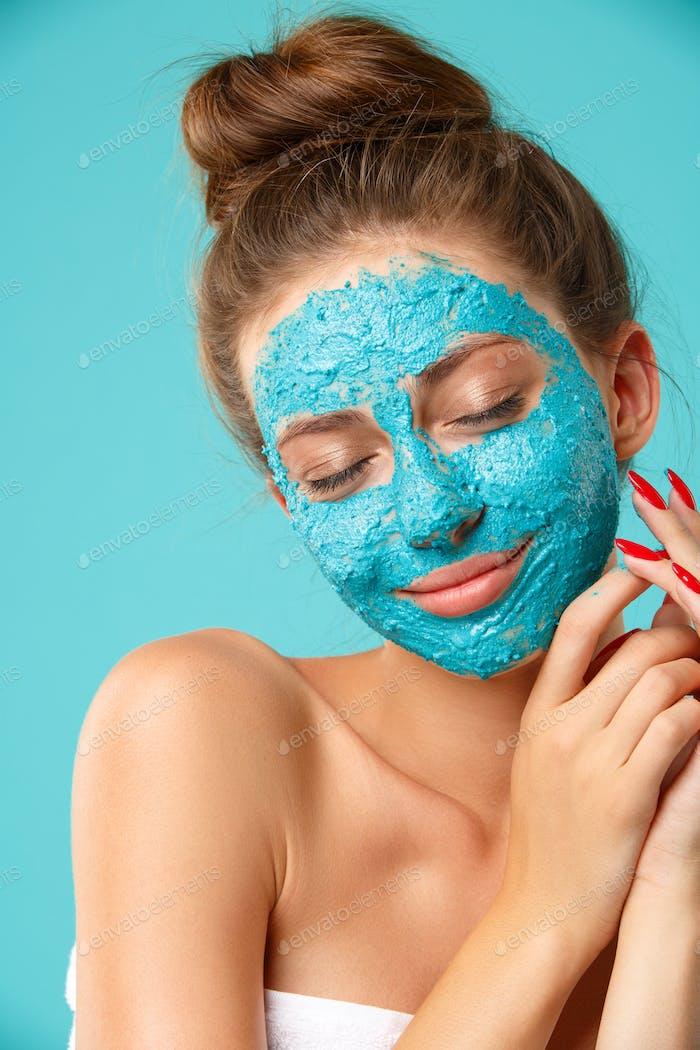 Beauty treatment - woman applying clay face mask