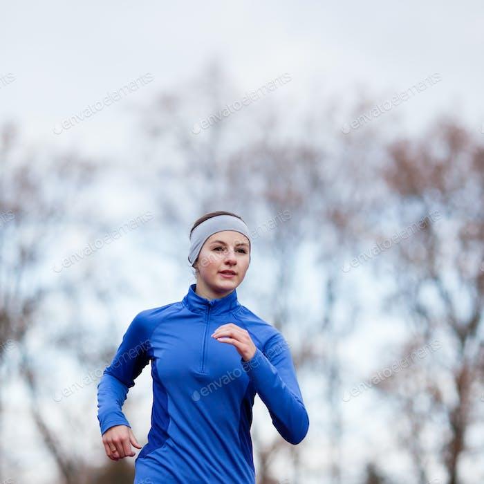 Porträt einer Frau läuft gegen den blauen Himmel