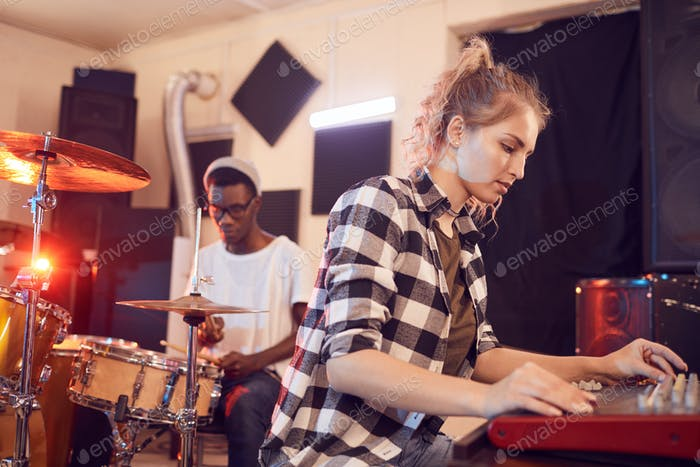 Young Woman Writing Music in Studio