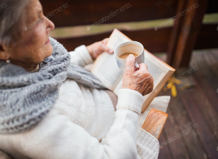 An elderly woman reading book outdoors on a terrace on a sunny day in autumn.