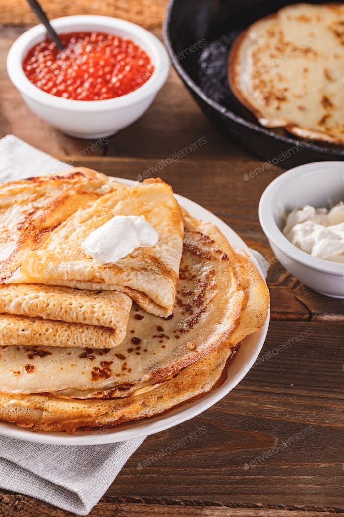 Stack of russian pancakes blini with red caviar, fresh sour cream