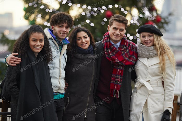 Portrait Of Young Friends On Walk Standing By Christmas Tree