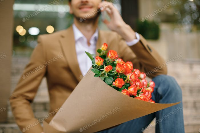 Focus on bunch of roses, folded in craft paper holded by man