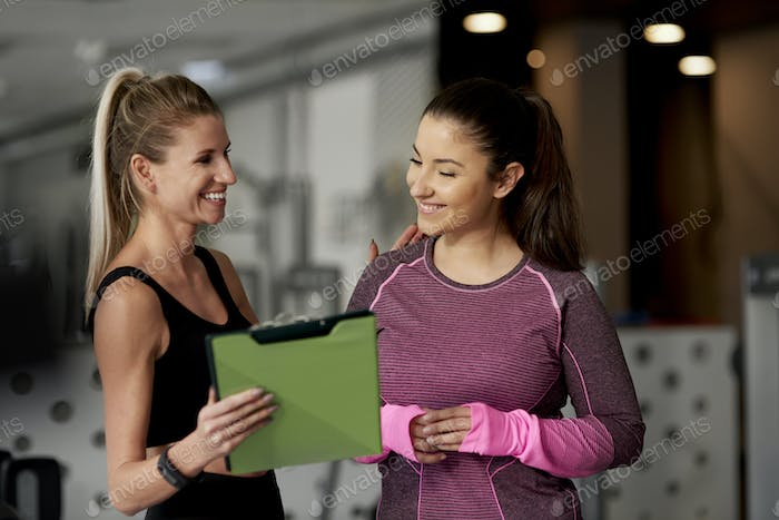 Cheerful instructor and woman at gym