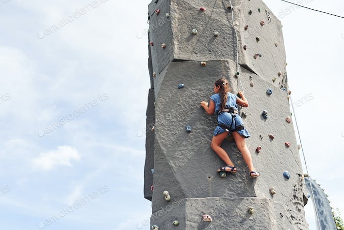 Little girl in casual blue clothes training rock climbing outdoors