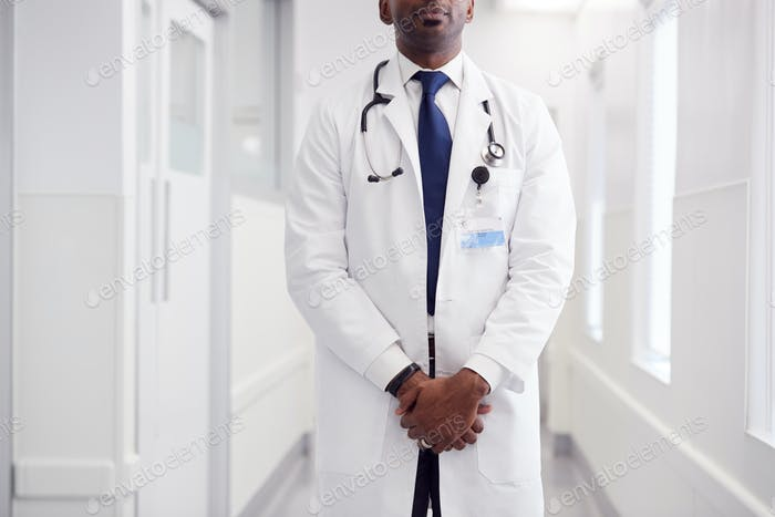 Close Up Of Mature Male Doctor Wearing White Coat Standing In Hospital Corridor