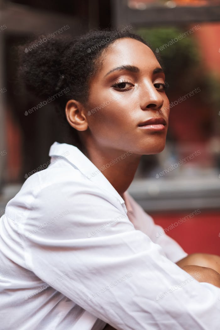 Portrait of beautiful african girl with dark curly hair in white