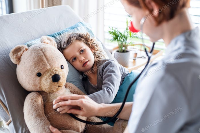 Friendly female doctor examining small girl in bed in hospital.