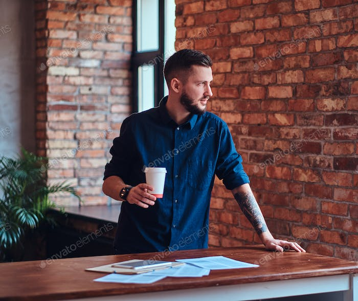 Handsome bearded man in office with loft interior.