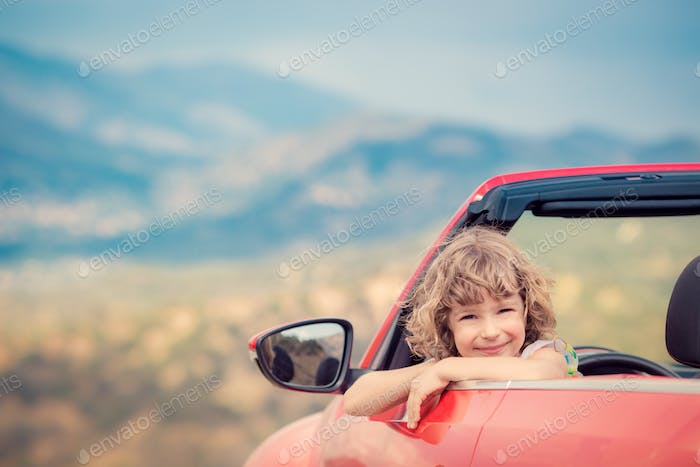 Happy child travel by car in the mountains