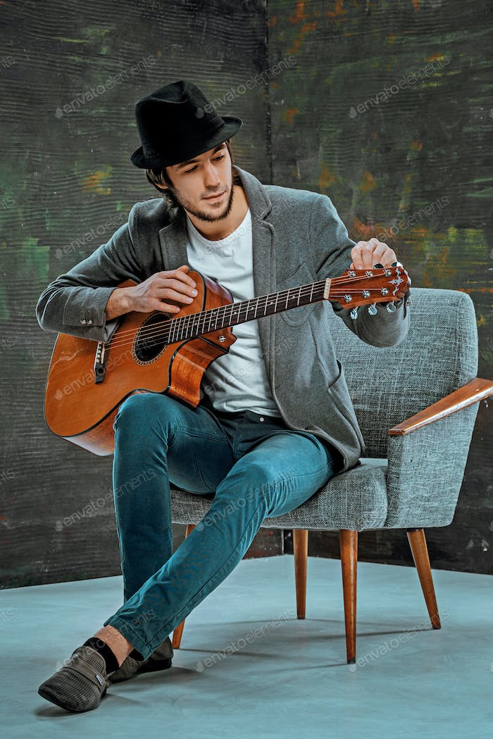 Cool guy with hat playing guitar on gray background