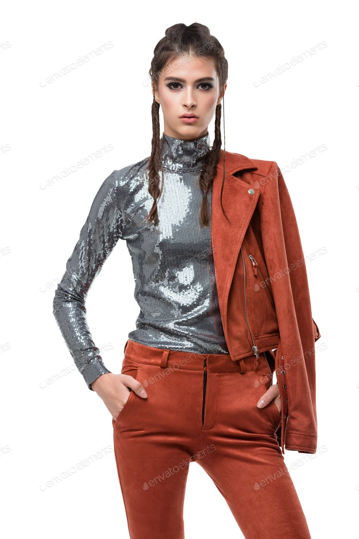 Pretty girl standing and thoughtfully looking in camera in light brown suede jacket and trousers