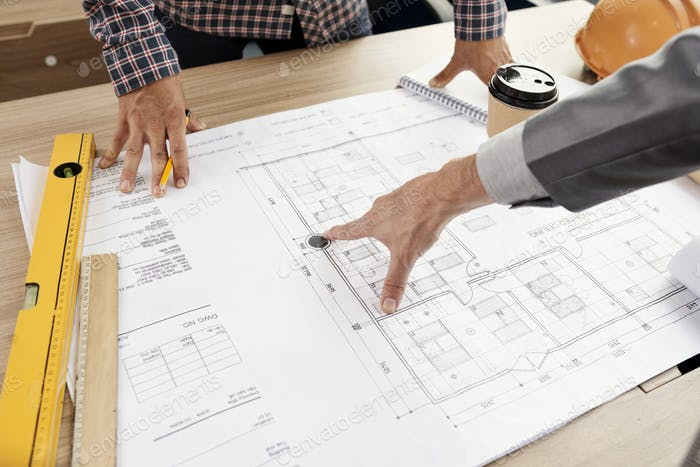 People examining construction blueprint