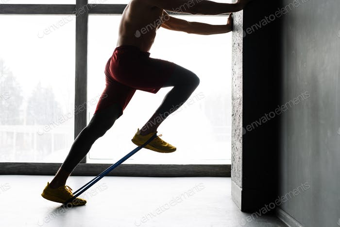 Young shirtless sportsman doing exercise with expander stretch tape