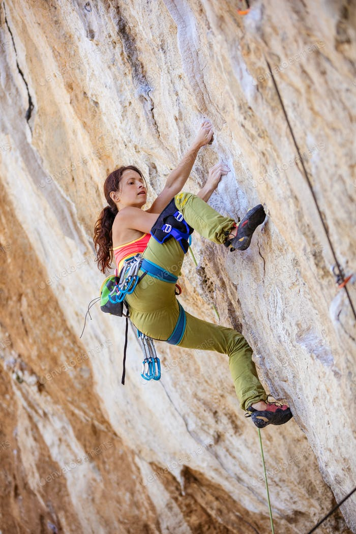Female rock climber on a challenging route on a cliff