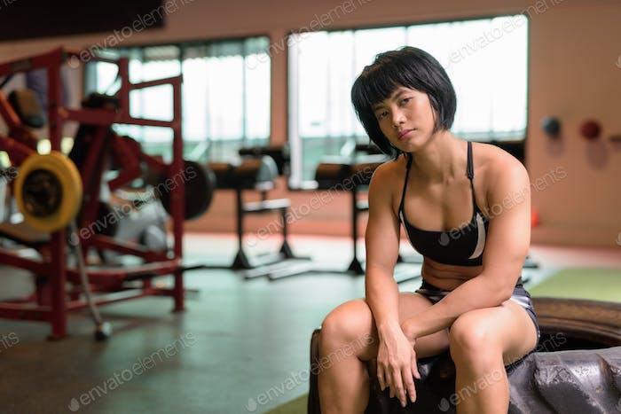 jóvenes hermosa asiático fitness mujer sentado en gimnasio