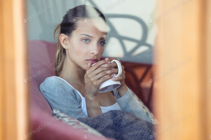 Serious young woman looking through the window while drinking coffee on the sofa at home.