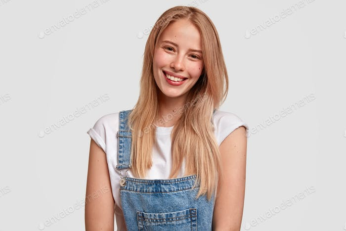 Glad European young female with satisfied expression, smiles broadly, has healthy pure skin, dressed