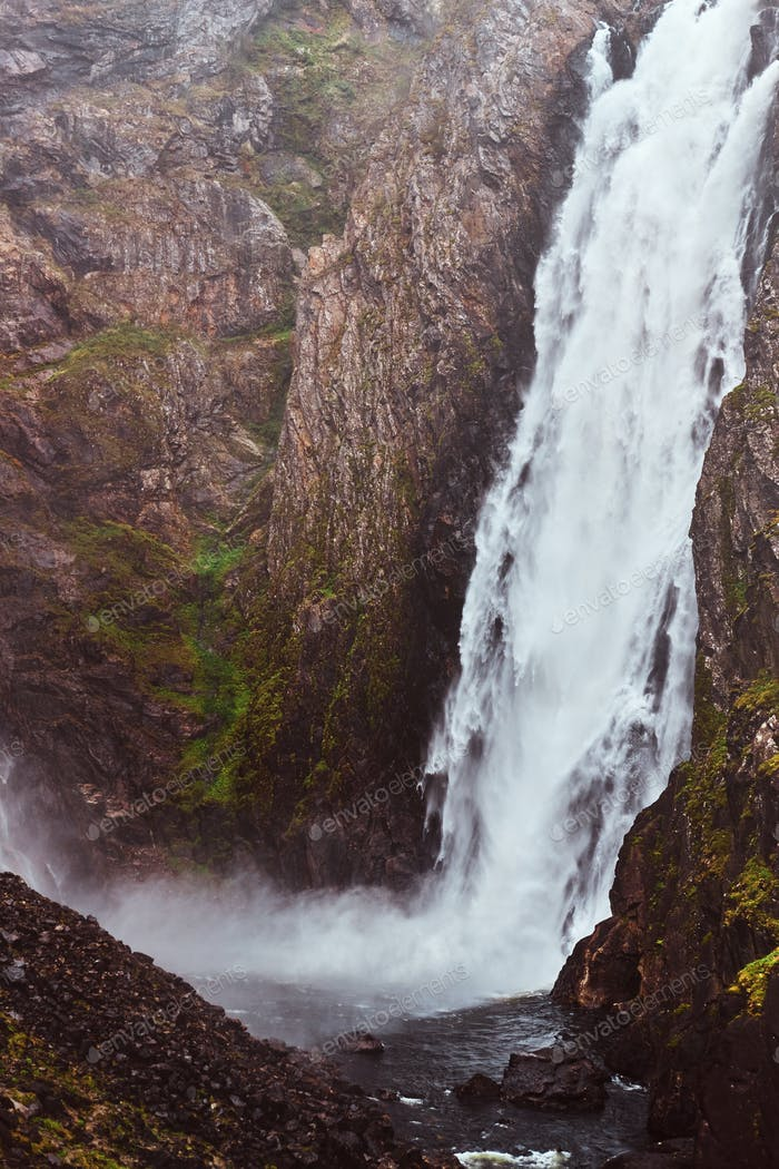 Waterfall in rocky mountains. Amazing nature in Norway.