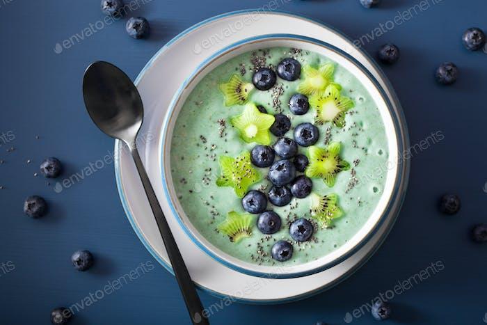 healthy spirulina smoothie bowl with blueberry, kiwi stars, chia