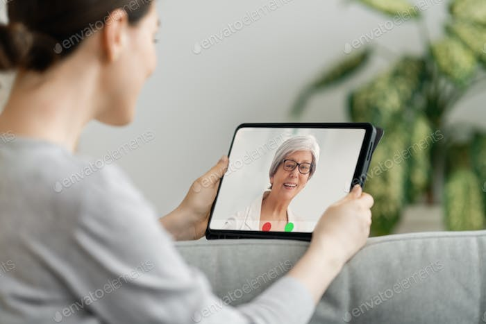 woman is using tablet pc for remote conversation with friends