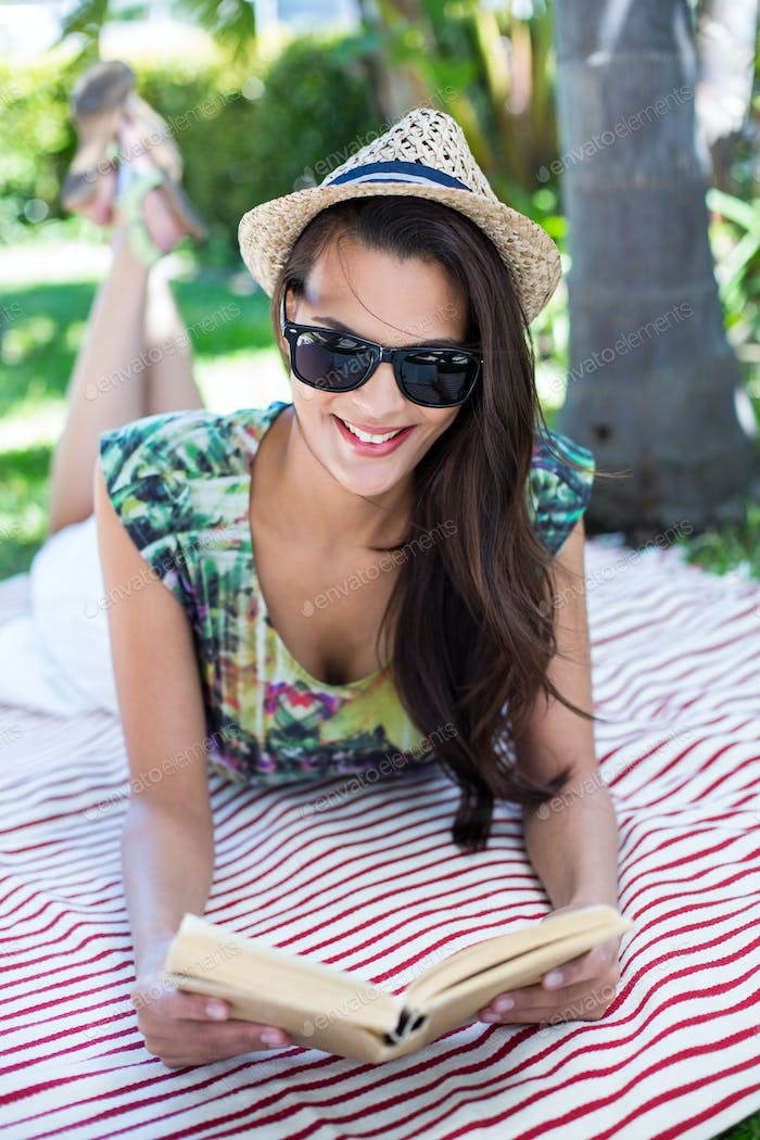 Smiling beautiful brunette lying and reading a book with palm tree behind her