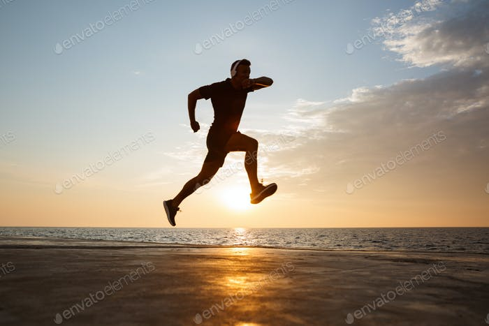 Silhouette of active sporty man 30s jumping and running along pi