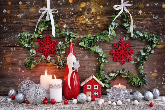 Christmas composition with candles, gnome figurine, photo frame and festive decorations