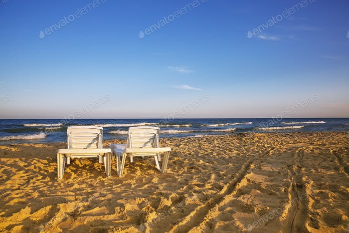 Two deckchairs on the sandy beach
