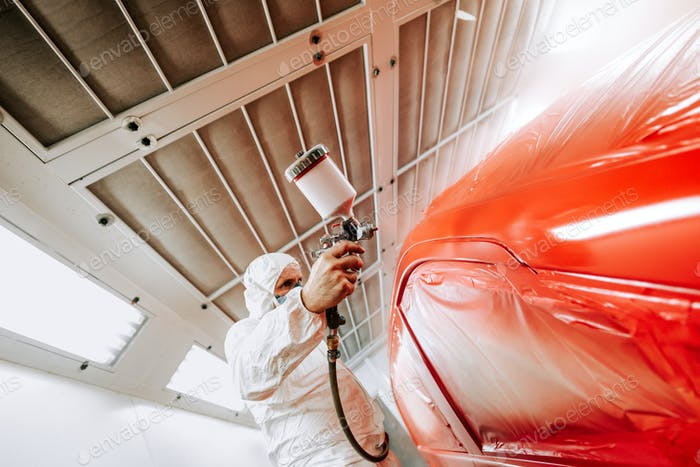 Automotive industry - auto engineer painting and working on a red body of car