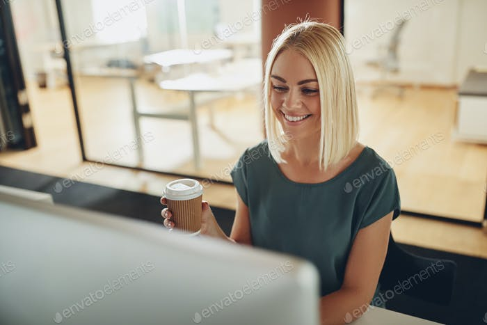 Smiling businesswoman enjoying a coffee while working in an office