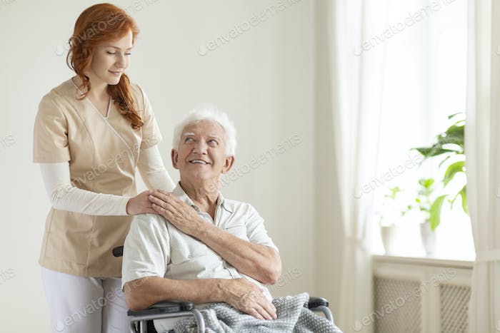 Smiling elderly man in a wheelchair and friendly caregiver in a