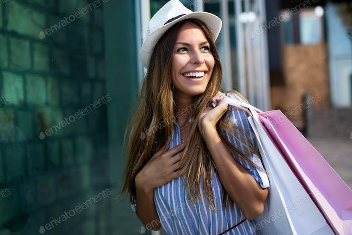 Shopping and tourism concept. Happy young oman with shopping bags