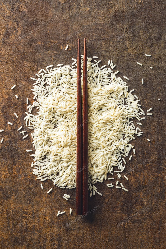 Uncooked indian long rice and chopsticks.