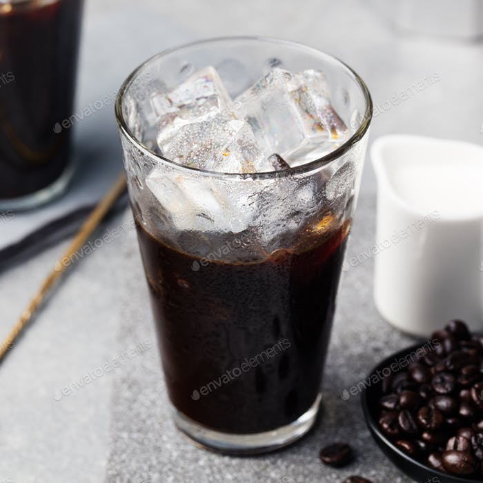 Ice coffee in a tall glass and coffee beans