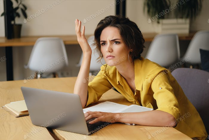 Young upset businesswoman sitting at the desk with laptop annoyed looking aside in office