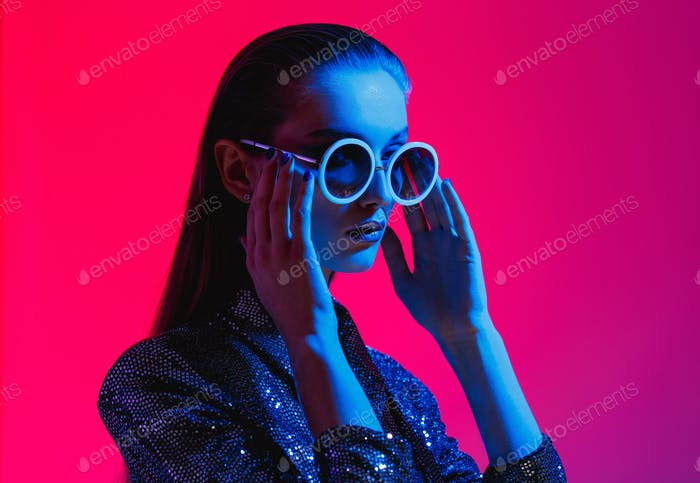 Fashion girl with long hair and round sunglasses in a black shining dress poses in neon light in the
