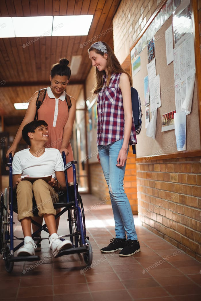 Schoolgirls talking with her disabled friend in corridor