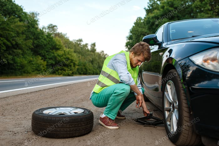 Car breakdown, young man repairing flat tyre